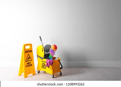 "Safety sign with phrase ""CAUTION WET FLOOR"" and mop bucket on floor near white wall. Cleaning tools"