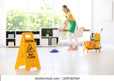 "Safety sign with phrase ""CAUTION WET FLOOR"" and young woman cleaning in office"