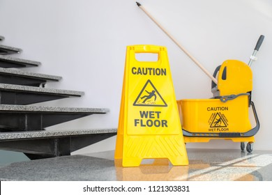 Safety sign with phrase Caution wet floor and mop bucket near stairs. Cleaning service