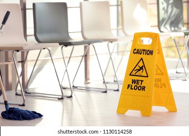 Safety sign with phrase Caution wet floor and mop, indoors. Cleaning service