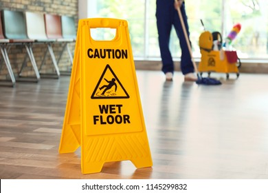 Safety sign with phrase Caution wet floor and blurred cleaner on background