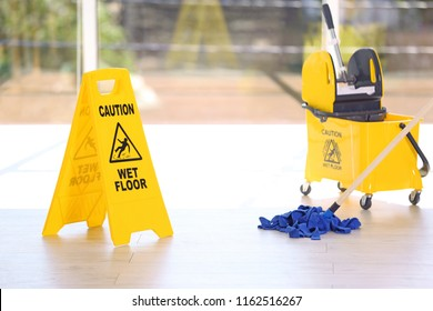 Safety sign with phrase Caution wet floor and mop bucket, indoors. Cleaning service