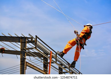 Safety sprinkling worker on high wear dresses and safety man with harness concept on steel structures success from work in site construction on blue sky background.