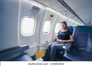 Safety travel. Young woman fasten belts while sitting in airplane seat.
