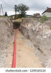 Safety tube with cables. Reconstruction site with trench for underground telephone optical lines
