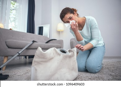 Safety violation. Adolescent woman being prone to dust allergies suffering from consequences of not wearing any personal protective equipment while cleaning dirty carpet