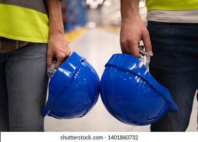 Safety at work. Head protection at work. Close up of two unrecognizable industrial workers holding hardhat protection helmets. Safety equipment at work concept.