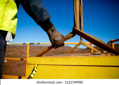 Safety work practices construction worker crane rigger wearing heavy duty glove holding safety control a two tones yellow lifting sling which its connecting to the load while crane is lifting
