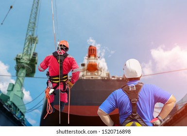 Safety, Worker Demonstration the Abseiling roped access of high wear equipment protective PPE with full safety harness in shipyard or factory by expertise, control and training  safety concept