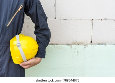 Safety in workplace concept. Industrial worker engineer or architect standing facing, wear workwear uniform or safety vest and hold a yellow safety helmet in hand with factory wall background.