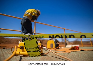 Safety workplace yellow striped caution tape sign barricade exclusion zone preventing from public access while construction worker welder welding repairing fence
