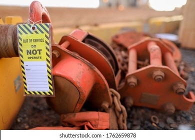 Safety workplaces yellow out of service tag attached on faulty damage defect of heavy duty lifting chains block at construction site Perth, Australia