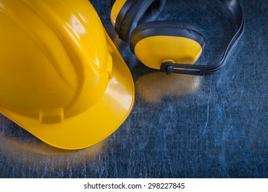 Safety yellow ear muffs and work helmet on scratched metallic background construction concept.