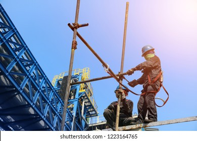 Safety,Construction wearing safety harness and Safety line working on a Metal indutry structure installed scaffolding