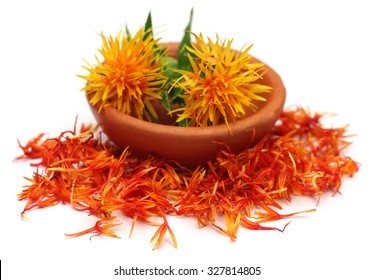 Safflower in a bowl over white background