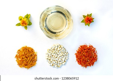 Safflower Carthamus tinctorius. Yellow, red dried petals, inflorescences, seeds and oil against a white background. View from above. Flat lay.