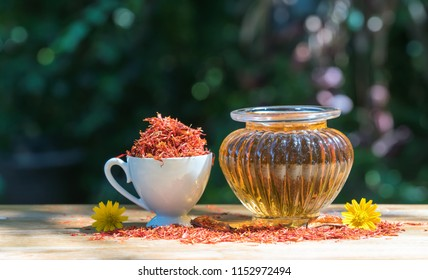 Safflower oil in glass bottle and safflower mortar on wooden  surface with  nature blurry background.