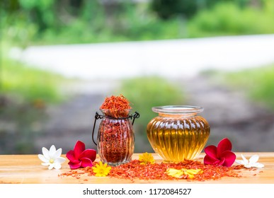 Safflower   oil  in  glass  bottle   on  wooden   surface  with  nature   blurry background.