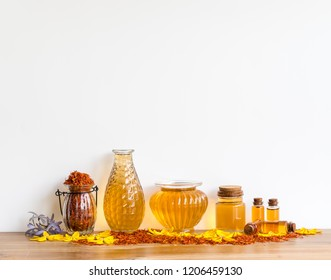 Safflower   oil  in  glass   bottles   on  wooden  surface  with  white  background.