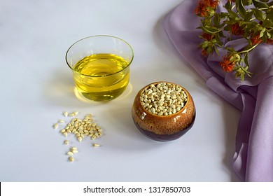 Safflower. Safflower oil, seeds in a container and scattered on a white surface and stems with flowers.