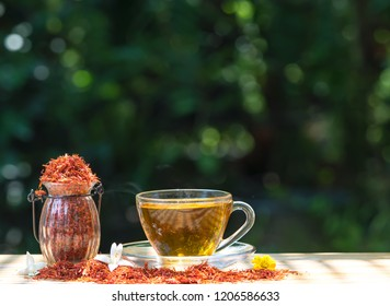 Safflower   tea   herb  for   reduce   cholesterol   in  glass  cup  on  wood   table  with  nature   blurry   background.