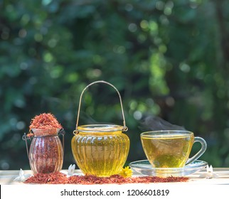 Safflower   tea   herb  for   reduce   cholesterol   in  glass  cup  on  wood   table  with  nature   blurry   background