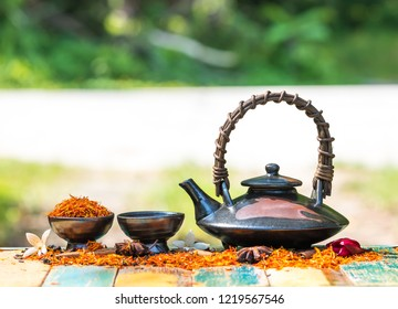 Safflower  tea  herb  for  reduce  cholesterol  in  brown  clay  teapot  and  cup  on  vintage  table  with  nature  blurry   background