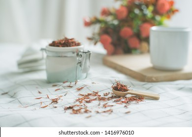 Safflower tea jar With a small wooden spoon and a white glass.