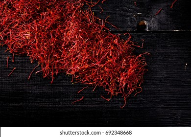 saffron crocus threads on black wooden board, view from above, backgrounds