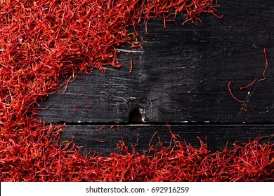 saffron crocus threads on black wooden background, full frame, view from above