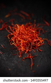 Saffron dry petals spices heap on dark slate stone table. Saffron flavor and coloring seasoning ingredient.
