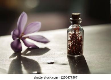 Saffron flower and dried saffron spice in a bottle