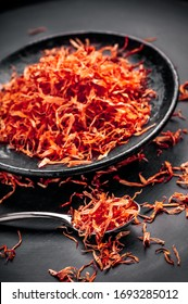 Saffron red petals spice tea flakes on black plate and dark background with silver metal spoon ready for seasoning and cooking vibrant color arrangement studio shot