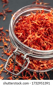 Saffron red petals spice tea flakes in glass jar and dark background ready for cooking or food seasoning vibrant color close up arrangement studio shot