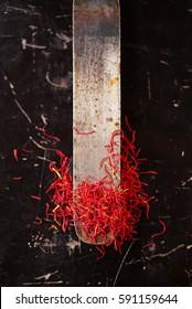 saffron space threads in vintage knife with dark metal background
