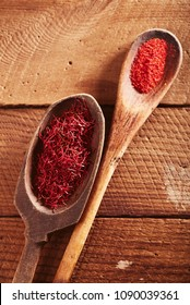 saffron space threads  in vintage wood spoons on wood plank background