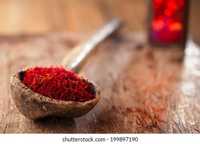 saffron spice in antique wooden spoon on old wood background, closeup