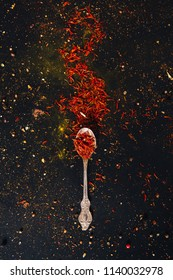 Saffron spice in spoon with empty space for text on dark black background. Seasonings for food. Close-up. Top view