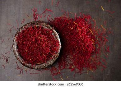 saffron spice threads and powder  in vintage iron dish  old metal background, closeup