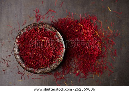 saffron spice threads and powder  in vintage iron dish  old metal background, closeup