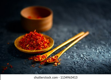 Saffron Spices. Saffron on black stone table in a wood bowl and a spoon. Spice and herbs on slate background. Seasonings, condiments. Cooking ingredients, flavor