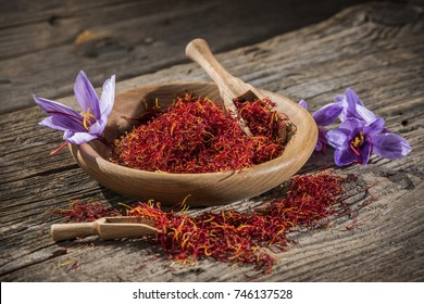 Saffron in wooden bowl on wooden table with saffron flowers on the side