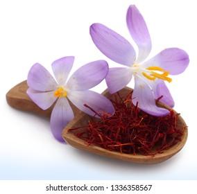 Saffron in a wooden scoop with crocus flower