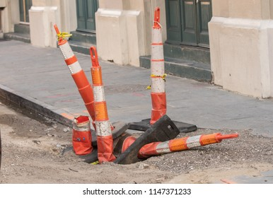 saftey cones cover a dangerous sink hole and trip hazard