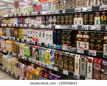 """Saga, JP - JULY 13, 2019: A lot of Japanese traditional alcohols or """"Sake"""" in the colorful paper packaging that sale on shelf as souvenirs in the liquor zone at a supermarket."""