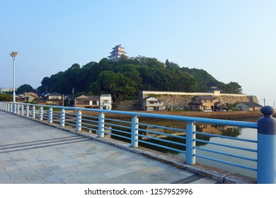 Saga, JP - JULY 19, 2018: The straight long walkway bridge with blue barriers that can see Karatsu Castle, the famous landmark in Karatsu City at the peak of mountain.