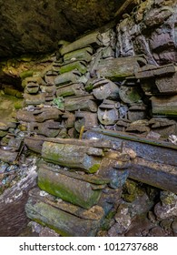 Sagada, Luzon, Philippines - 4/29/2015: Molding wooden coffins carved by Igorot people, a 2000+ year tradition, are stacked along the walls in Sumaguing Cave at Sagada, Luzon, Philippines.