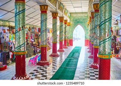 SAGAING, MYANMAR - FEBRUARY 21, 2018: The market hall of Kaunghmudaw Pagoda, decorated with fine mirrorwork, religious paintings and colored columns, on February 21 in Sagaing.