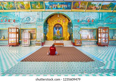 SAGAING, MYANMAR - FEBRUARY 21, 2018: The prayer hall of Eastern Image House of Kaunghmudaw Pagoda with paintings of Buddha life, miror patterns and carved altar gate, on February 21 in Sagaing.