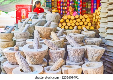 SAGAING, MYANMAR - FEBRUARY 21, 2018: Stall of Kaunghmudaw Pagoda market with kyauk pyin mortars and pestles for grinding thanaka and producing traditional cosmetic paste, on February 21 in Sagaing